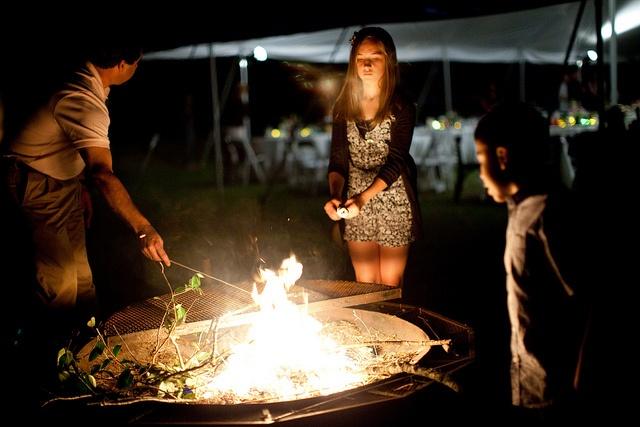 Faire griller des marshmallows atour du feu pour préparer des smores américains